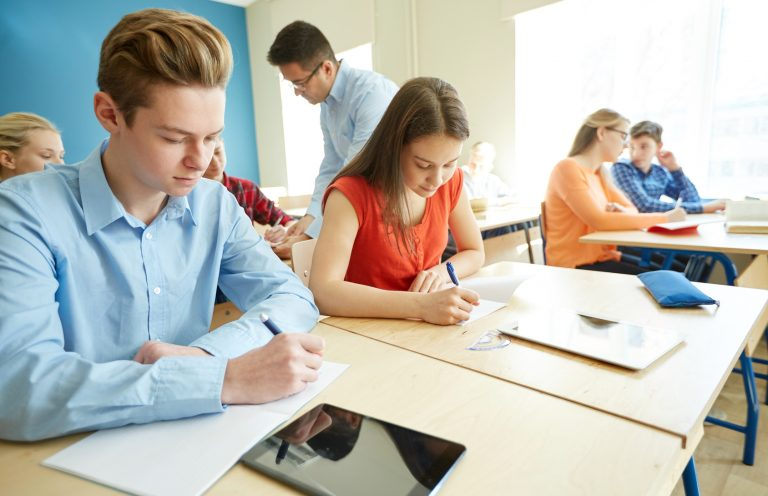 education, school, learning, teaching and people concept - group of students writing test or exam and teacher in classroom