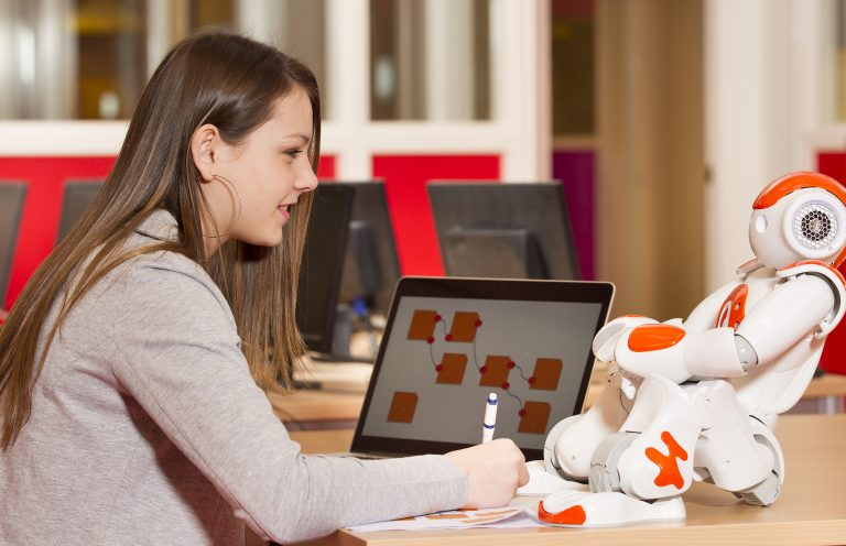 Young teen girl playing with humanoid robot during school time